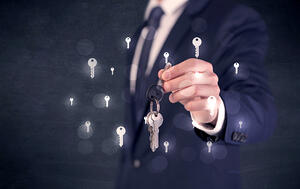 Businessman in suit holding keys with keys graphics around and dark background