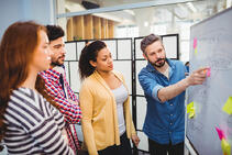 Executive explaining strategy to colleagues on whiteboard in creative office